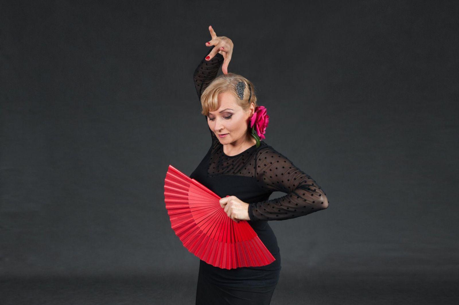 Fotografia kobiety w hiszpańskiej sukni w pozie tanecznej. Ma uniesioną dłoń ponad głową, w drugiej trzyma wachlarz.