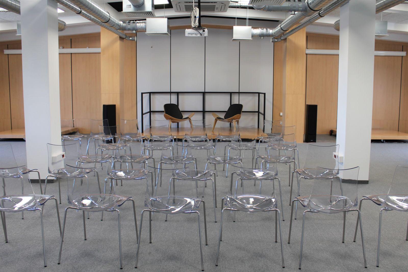 Fotografia sali konferencyjnej. Przeźroczyste krzesła w jasnym pomieszczeniu. Na środku scena.