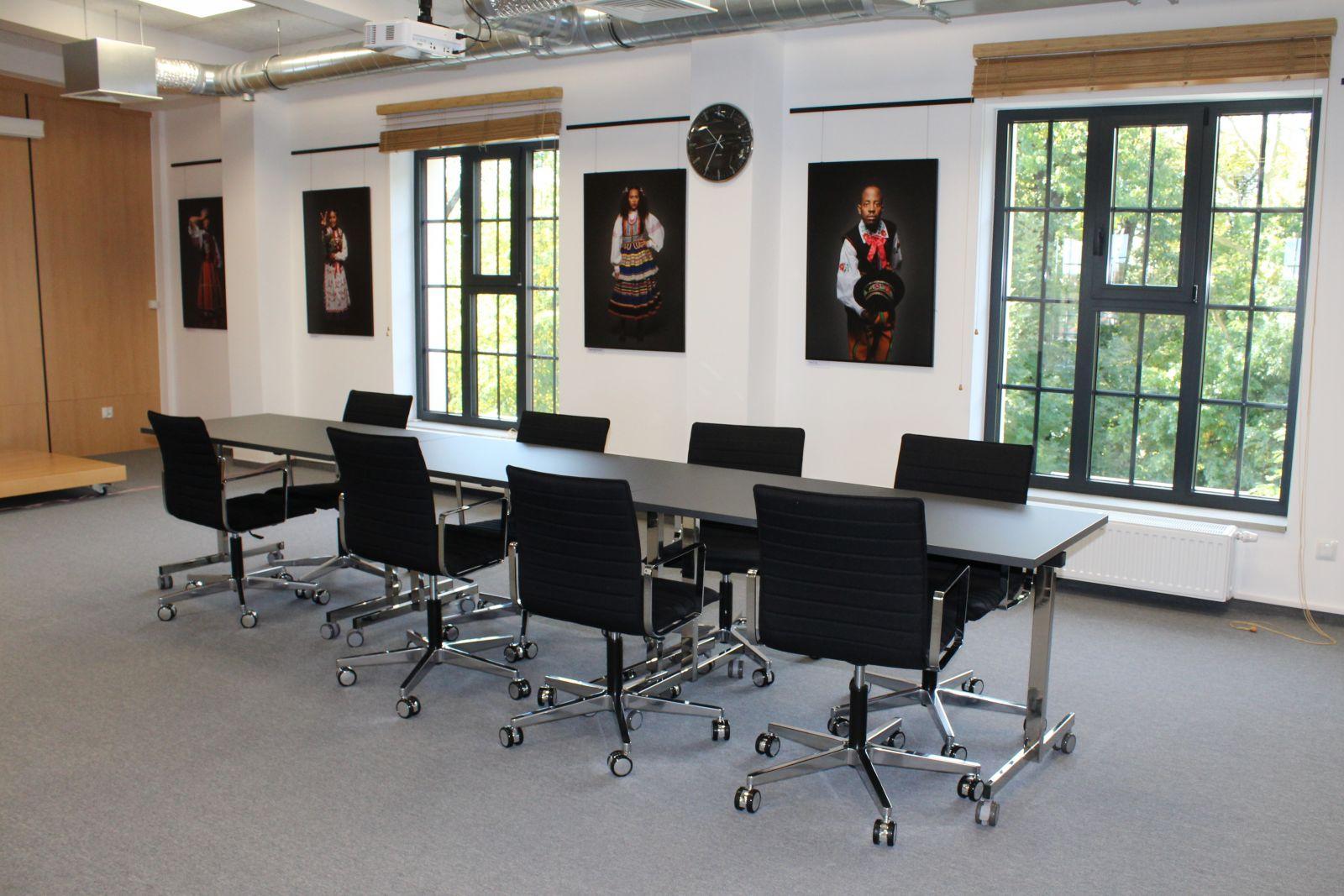 Fotografia sali konferencyjnej. Czarne krzesła w jasnym pomieszczeniu. Na ścianie kolorowe fotografie.
