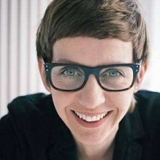 Fotografia Magdaleny Grzebałkowskiej. Uśmiechnięta kobieta w okularach.