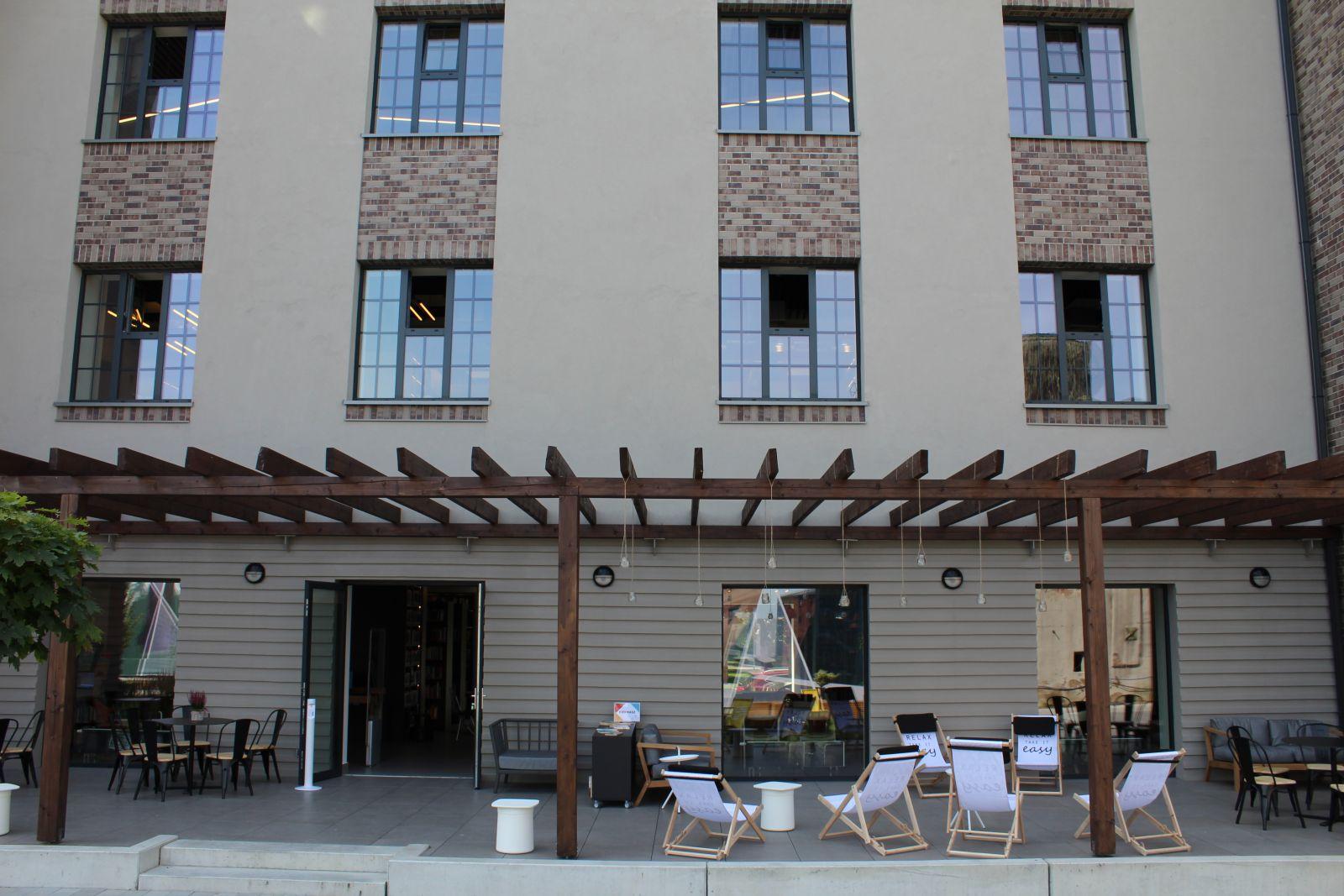 Fotografia tarasu przed biblioteką. Widoczna trawa, duże okna i drewniana pergola.