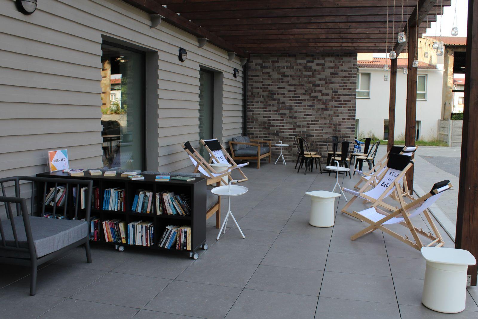 Fotografia tarasu przed biblioteką. Widoczne krzesła, leżaki i drewniana pergola.