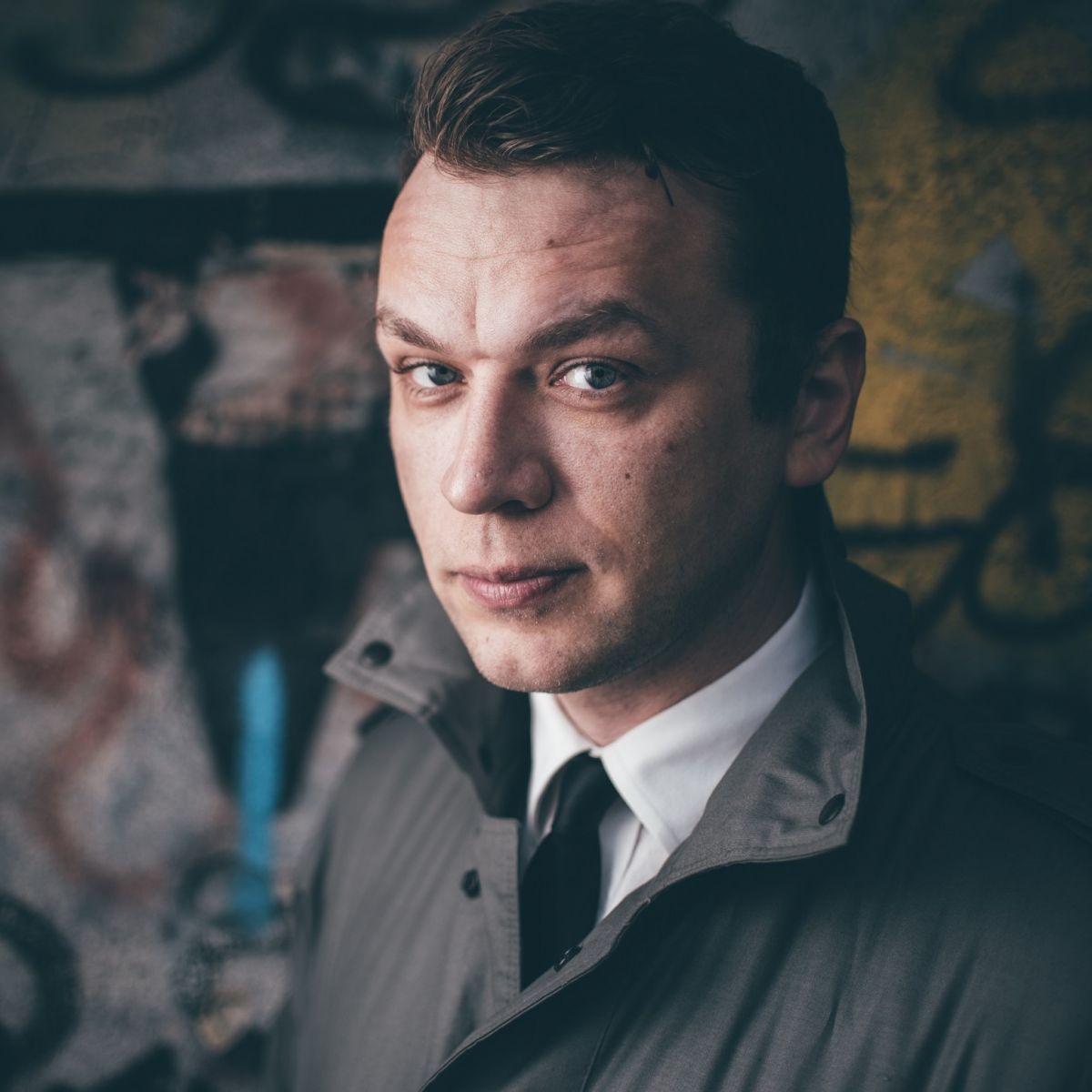 Fotografia Marcela Woźniaka. Mężczyzna na ciemnym tle.