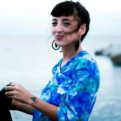 Młoda, uśmiechnięta dziewczyna w spiętych włosach i lekkiej sukience.