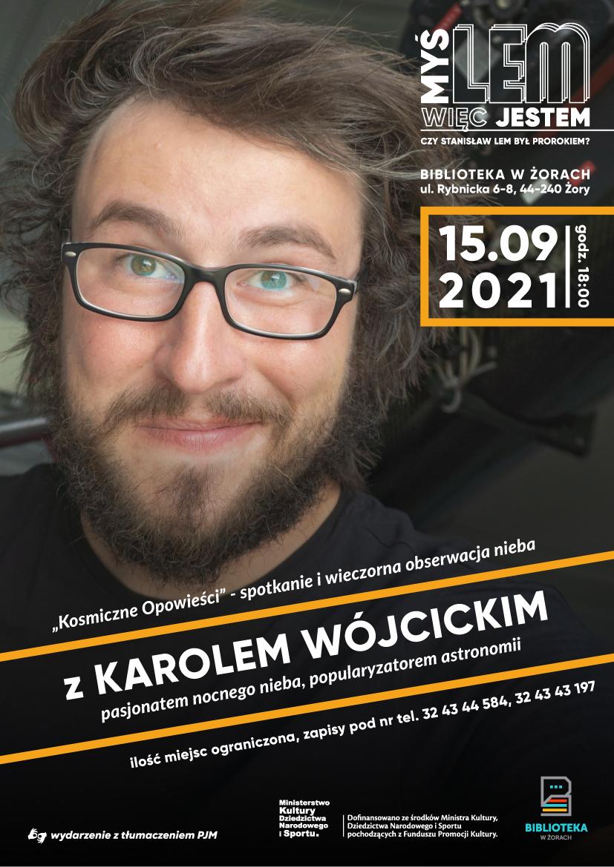 Plakat ze zdjęciem Karola Wójcickiego. Mężczyzna ma krótkie, rozwiane w bok włosy, okulary, jest uśmiechnięty i patrzy prosto w obiektyw.