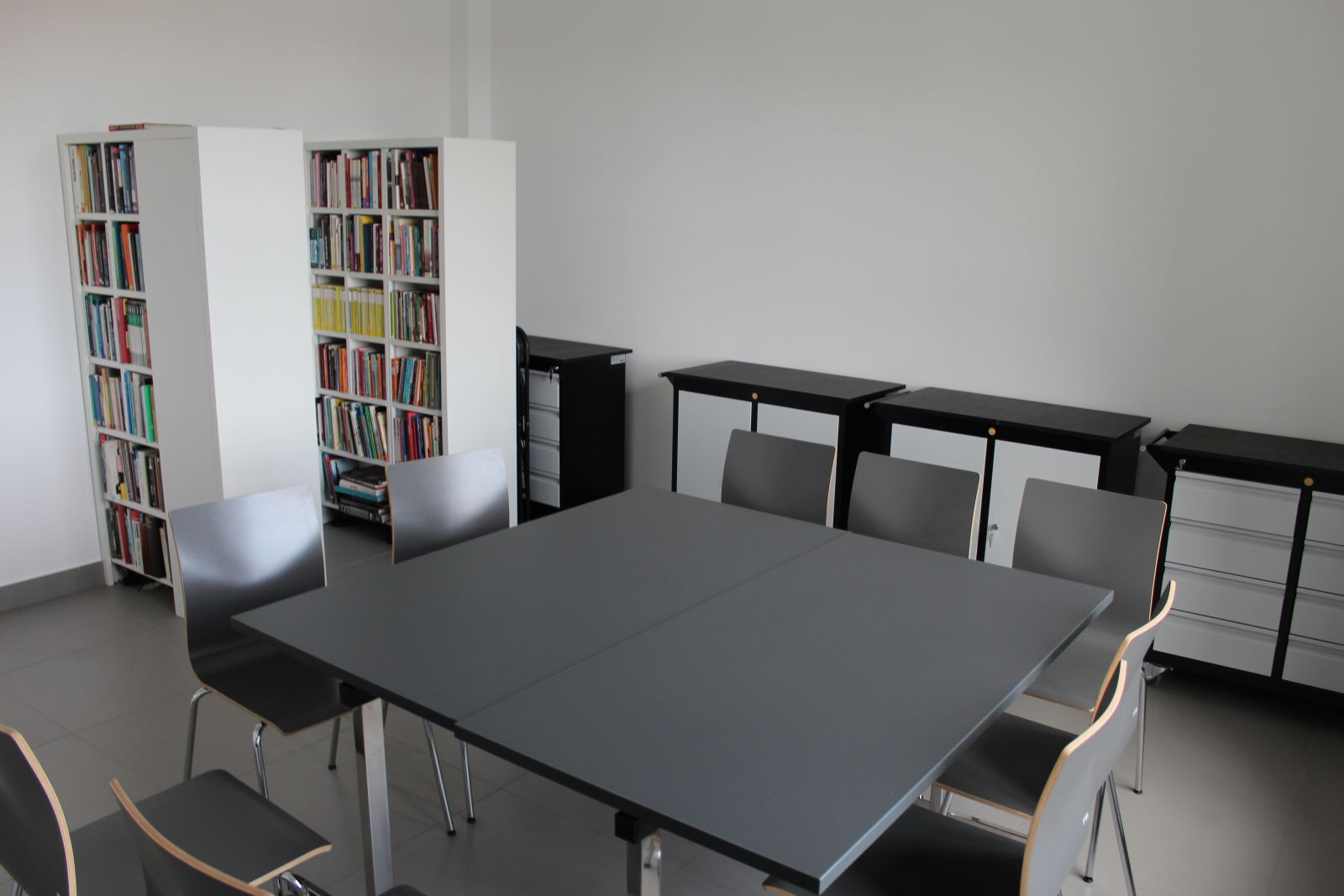 Fotografia sali z krzesłami i stołami. Pomieszczenie jasne i nowoczesne.