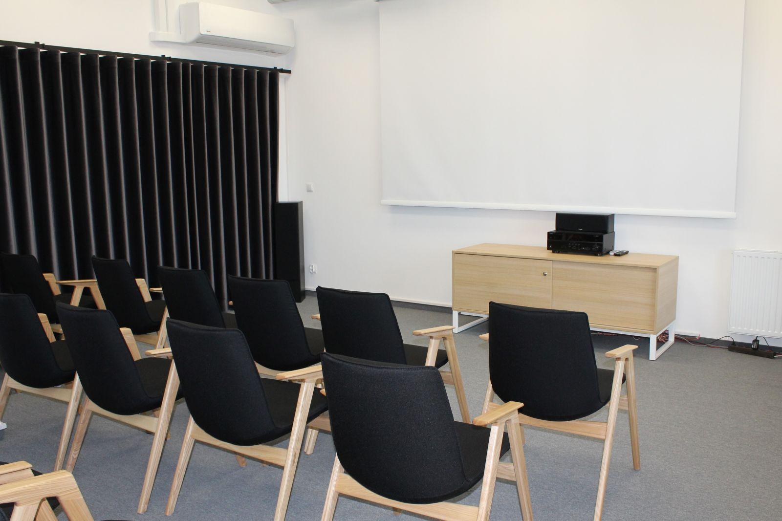 Fotografia sali projekcyjnej. Widoczne czarne krzesła i ekran projekcyjny.