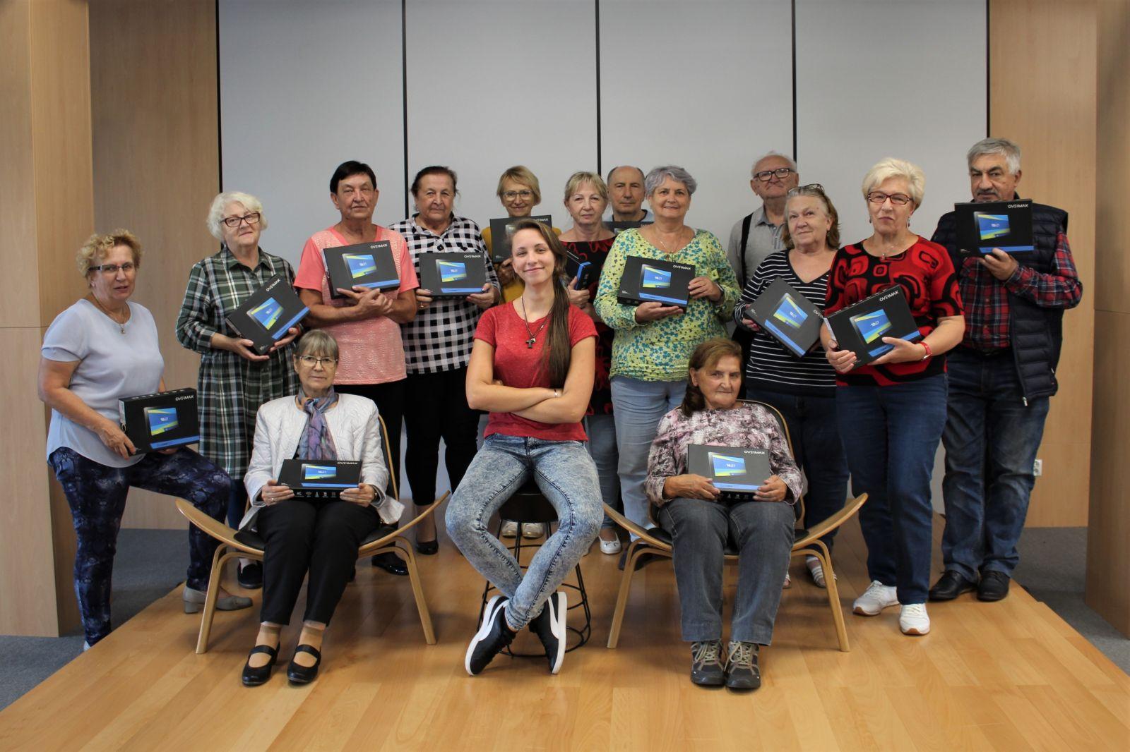 Fotografia grupy starszych ludzi trzymających w rękach pudełka z tabletami.