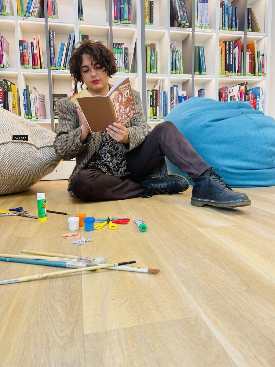 Młoda kobieta siedzi na podłodze i czyta książkę. Przed nią są rozłożone różne przybory plastyczne: pędzle, klej w sztyfcie, farby i nożyczki. Za nią widoczne są duże, miękkie pufy i regał z książkami.