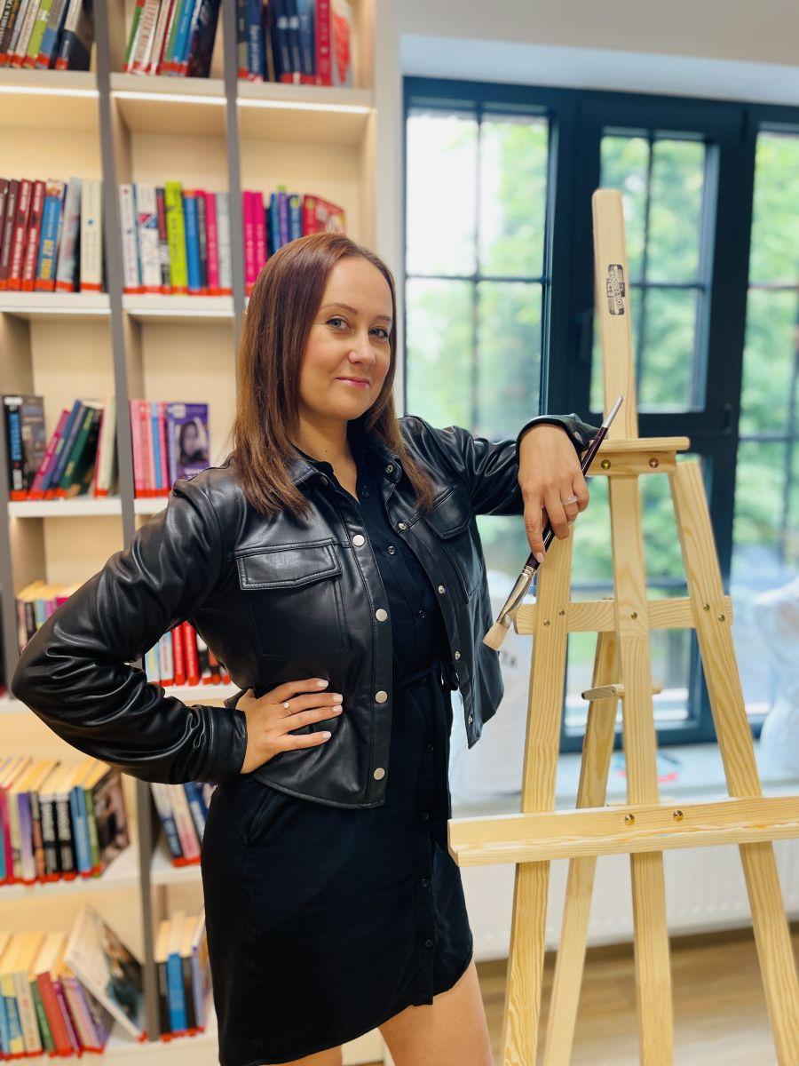 Młoda dziewczyna w długich włosach, ubrana w skórzaną kurtkę i spódnicę stoi przy drewnianej sztaludze. W tle widoczne regały z książkami.