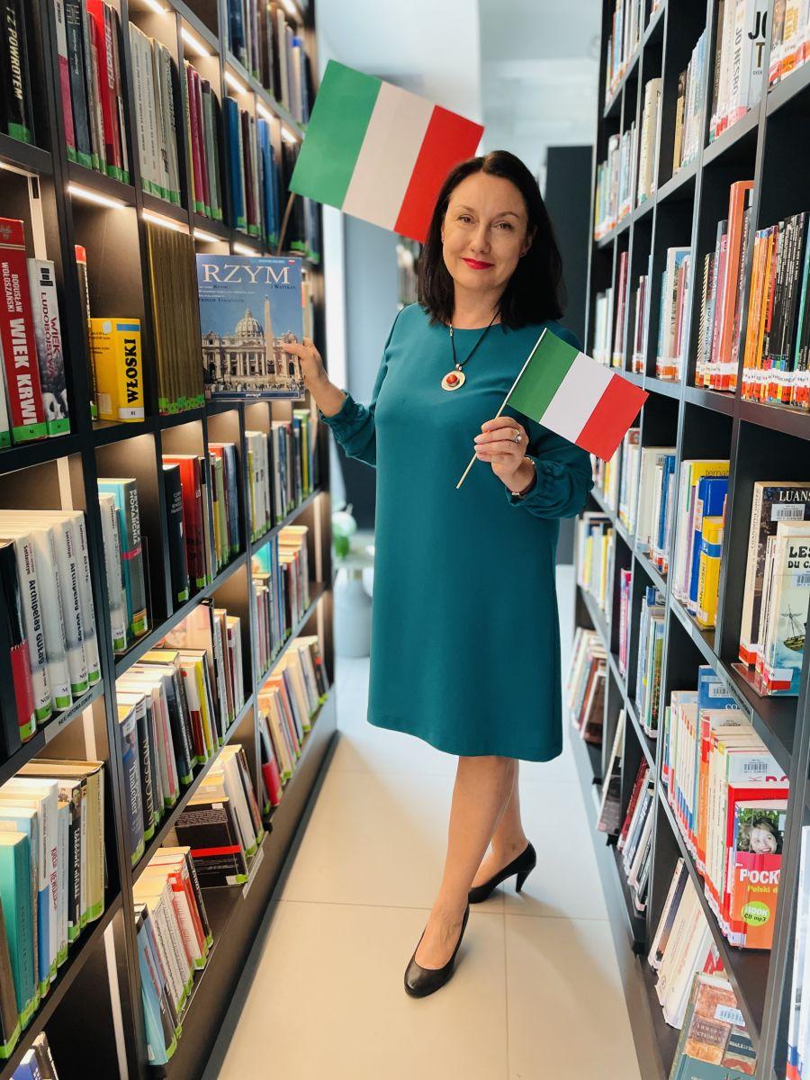 Kobieta w średnim wieku ubrana w sukienkę z długim rękawem trzyma w rękach dwie włoskie flagi i książkę o Rzymie. Stoi pomiędzy regałami z książkami.