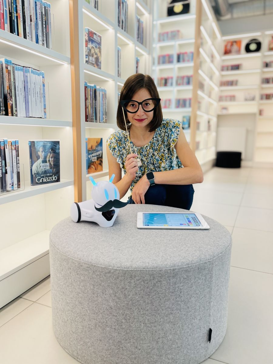 Młoda dziewczyna w krótkich włosach przykłada do swoich oczu okulary na patyku wykonane z papieru. Dziewczyna kuca przy pufie, na której leży robot i tablet. Robot ma założone papierowe wąsy. W tle stoją regały, a na nich są pudełka z płytami.