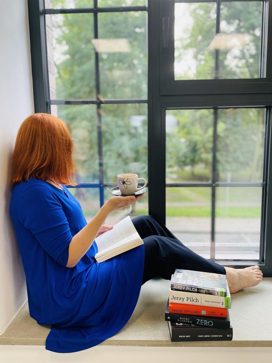 Kobieta siedzi na parapecie z ugiętymi nogami i patrzy w okno. W dłoni trzyma filiżankę, a w drugiej otwartą książkę opartą o uda. Obok jej nóg leży stos książek.
