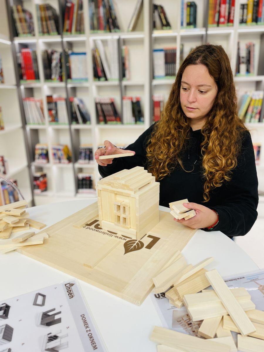 Młoda dziewczyna siedzi przy stole i układa drewniane klocki w kształt domu. Z tyłu widoczne są regały z książkami.