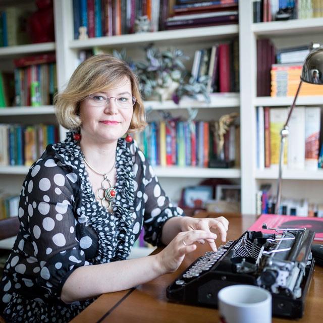 Fotografia portretowa Anny Czerwińskiej-Rydel: uśmiechnieta kobieta siedząca przy maszynie, w tle widoczne książki.